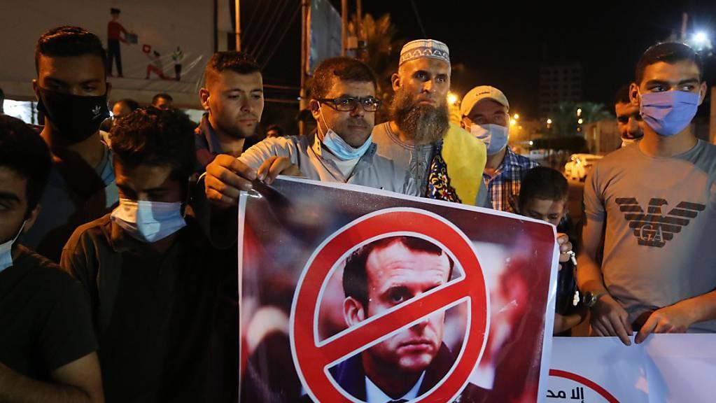 Ein Palästinenser hält bei einer Protestaktion ein Anti-Macron-Plakat.