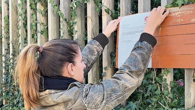 Eine Helferin befestigt im Martinsberg in Baden ein Plakat.
