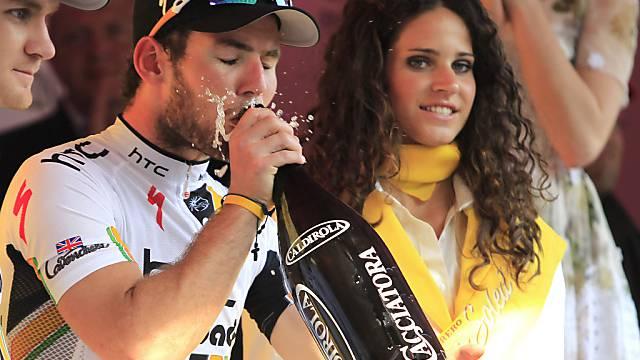 Gesamtleader Mark Cavendish trinkt einen Schluck Champagner.
