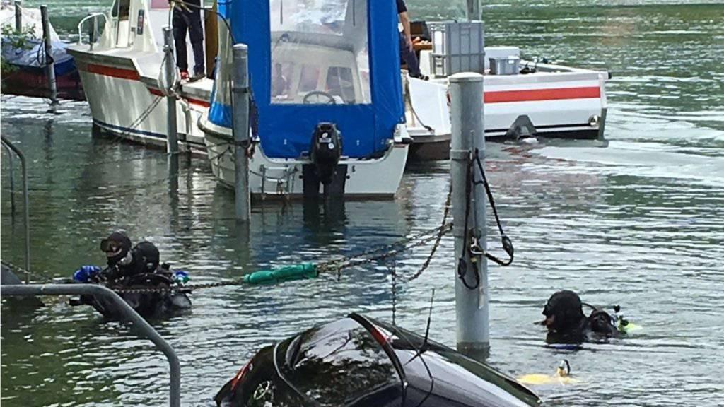 Taucher der Seepolizei der Berner Kantonspolizei und des Rettungsdienstes Bielersee sichern das Auto, um ein weiteres Abtreiben zu verhindern.
