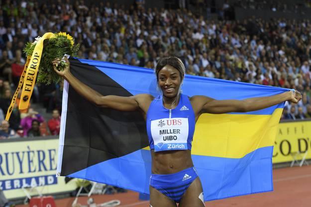 Stolz präsentiert sich die Läuferin nach ihrem Sprint ins Ziel mit der Bahamas-Flagge.