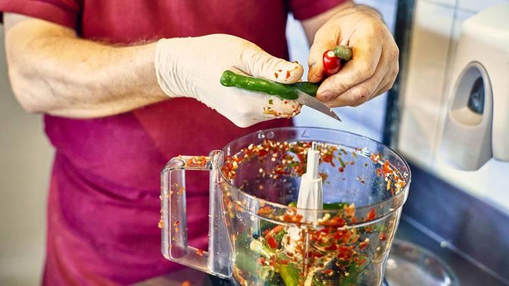Eine scharfe Sache: Peperoncini halbieren für die Sauce in der Menage.