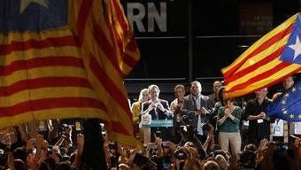 Regierungschef Artur Mas tritt vor Anhängerinnen und Anhänger und verkündet den Sieg seiner Wahlallianz. Tausende Menschen gingen am Sonntagabend in Barcelona auf die Strasse, um zu feiern.