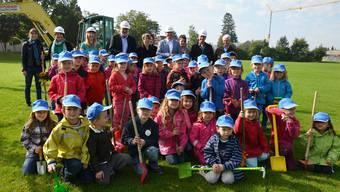 Spatenstich: Die Kindergartenkinder posieren mit ihren von der Gemeinde spendierten Käppi vor dem Gemeinderat und Gästen.