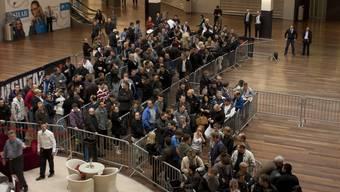 Zahlreiche Frühaufsteher stehen Schlange, um in den Saturn-Markt zu kommen.