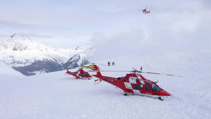 Zwei Helikopter der Rettungsflugwacht Rega und einer der Heli Bernina im Einsatz nach einem Lawinenunglueck am Piz Vilan.