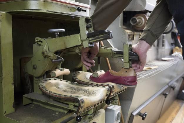 Mit einem Holzmodell wird der Schuh an der Maschine angepasst.