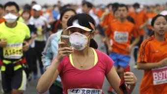 Eine Teilnehmerin des Peking-Marathons filmt den Lauf mit ihrem Smartphone. Mittels Handydaten wollen Forscher die Luftverschmutzung in Städten bestimmen. (Archiv)