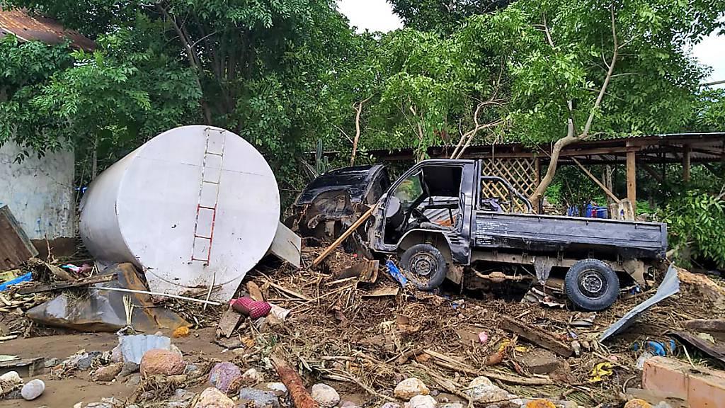 Das Wrack eines Pick-ups liegt auf einem Haufen Trümmern. Foto: Rofinus Monteiro/AP/dpa