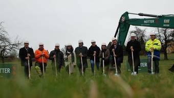 Vertreter von Politik, Bauverwaltung, Planungsbüro und Baufirmen nehmen den Spatenstich vor.