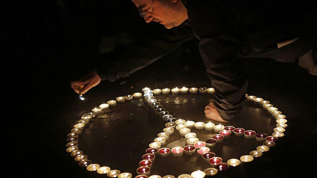 """Ein Mann zündet Kerzen für die Opfer der Terror-Anschläge in Paris an. In einer einstimmig verabschiedeten Resolution des Weltsicherheitsrates werden alle """"dazu fähigen Staaten"""" aufgefordert alle nötigen Massnahmen im Kampf gegen die IS-Terrormiliz zu ergreifen."""