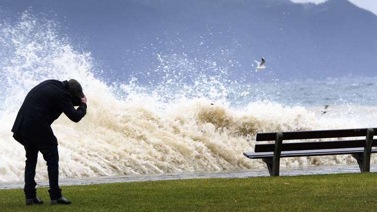 Ein Mann duckt sich vor einer grossen Welle in Vevey am Genfersee.