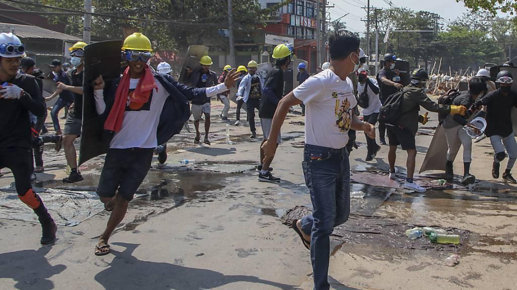 Anti-Putsch-Demonstranten ziehen sich von den behelfsmäßigen Barrikaden zurück, nachdem Bereitschaftspolizisten Schallbomben und Gummigeschosse abgefeuert haben. Foto: Uncredited/AP/dpa