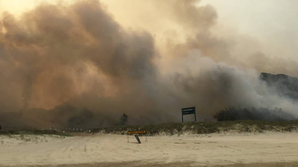 A supplied image obtained on Monday, December 7, 2020, the K'gari (Fraser Island) bushfire seen outside the Cathedrals camping ground, on Fraser Island. TA dangerous bushfire is within a few hundred metres of Happy Valley as dozens of firefighters battle to save the township on Queensland's Fraser Island.. (AAP Image/Supplied by QLD Ambulance Service) NO ARCHIVING, EDITORIAL USE ONLY