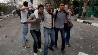 Demonstranten helfen in Kairo einem Verletzten