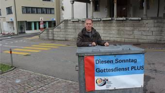 Pfarrer Ruszkowski mit dem Abfallcontainer, der zum Gottesdienst einlädt.
