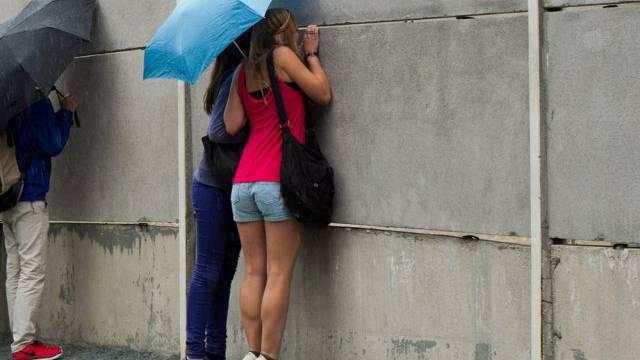 Touristen äugen durch die Überresten der Berliner Mauer