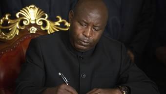 Evariste Ndayishimiye, designierter Präsident von Burundi, unterzeichnet im Präsidentenpalast das Kondolenzbuch. Foto: Berthier Mugiraneza/AP/dpa