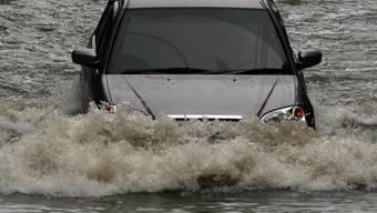 Ein Auto kämpft sich durch die Strassen Bangkoks