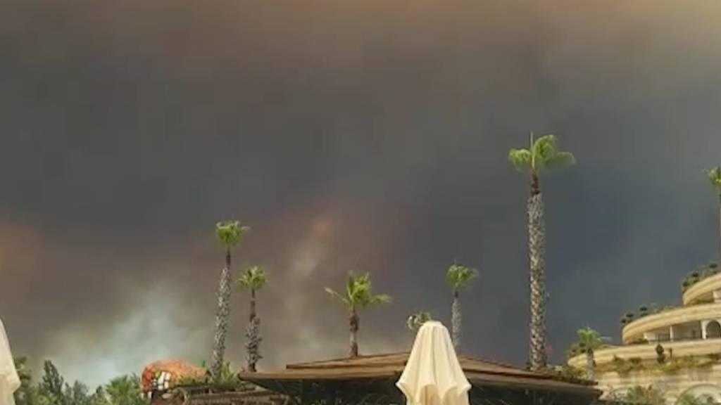 Dunkler Rauch zieht über einen Hotelkompex in der türkischen Urlaubsregion Antalya hinweg. Winde trieben die Flammen mehrerer Waldbrände in Richtung der Wohnbezirke, wie der Landrat des Bezirks Manavgat dem Sender CNN Türk sagte. Foto: Cevin Dettlaff/dpa-Zentralbild/dpa