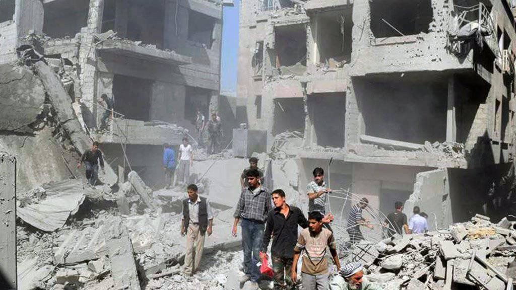 Bewohner eines Viertels der syrischen Hauptstadt Damaskus begutachten den Schaden nach einem mutmasslichen Regierungsangriff. Ein US-Sondergesandter unternimmt einen weiteren Anlauf für eine friedliche Lösung des Konflikts. (Archivbild)