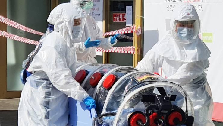 Ein Patient, der mutmasslich am neuen Coronavirus COVID-19 erkrankt ist, wird in ein südkoreanisches Spital eingeliefert. Dort wurden 31 neue Infektionsfälle registriert. In China ist die Zahl der Neuerkrankungen dagegen stark gefallen. (Foto: Yonhap/EPA Keystone-SDA)