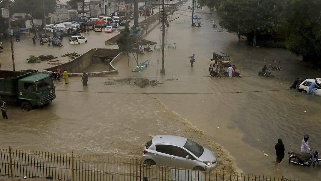 Eine überschwemmte Straße in der pakistanischen Hafenstadt Karatschi. Foto: Fareed Khan/AP/dpa