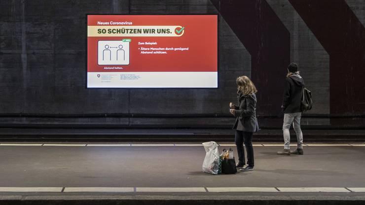 Eine Werbetafel macht im karg bevölkerten Bahnhof Bern auf die Hygiene-Tipps des Bundesamts für Gesundheit aufmerksam.