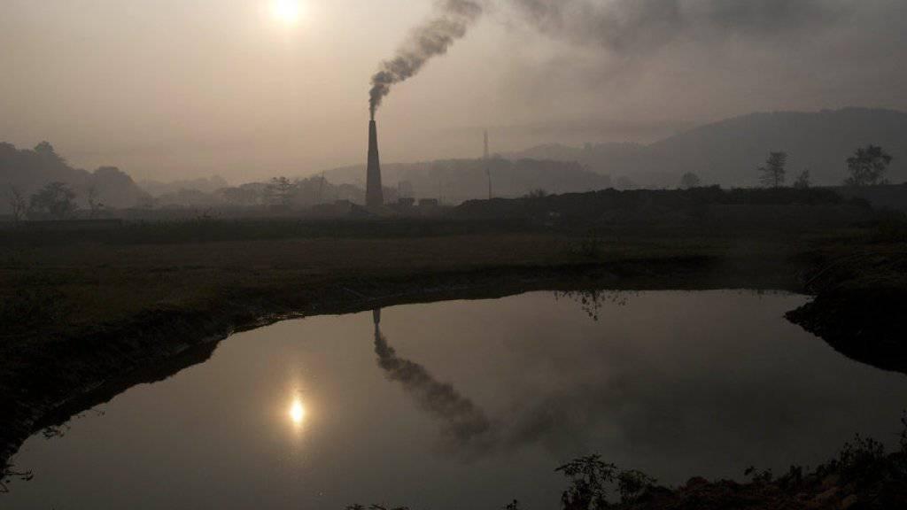 Blick auf den Kamin einer Ziegelsteinfabrik nahe der indischen Stadt Gauhati. Gemäss Experten hat die Konzentration gefährlicher Treibhausgase in der Erdatmosphäre einen neuen Höchststand erreicht. Die Gase stammen unter anderem aus Industrie und Landwirtschaft (Archiv)