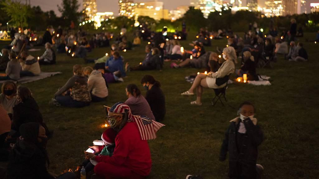 Menschen versammeln sich auf einem Rasen während einer Gedenkveranstaltung an die verstorbene Richtern Bader Ginsburg. Foto: Jeff Wheeler/Star Tribune/AP/dpa