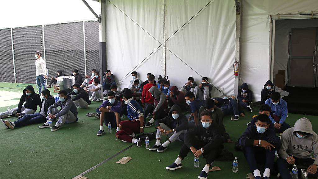 Minderjährige Kinder, die positiv auf Covid-19 getestet wurden, sitzen vor der Aufnahmeeinrichtung für unbegleitete minderjährige Migranten im Rio Grande Valley. Foto: Dario Lopez-Mills/Pool AP/dpa