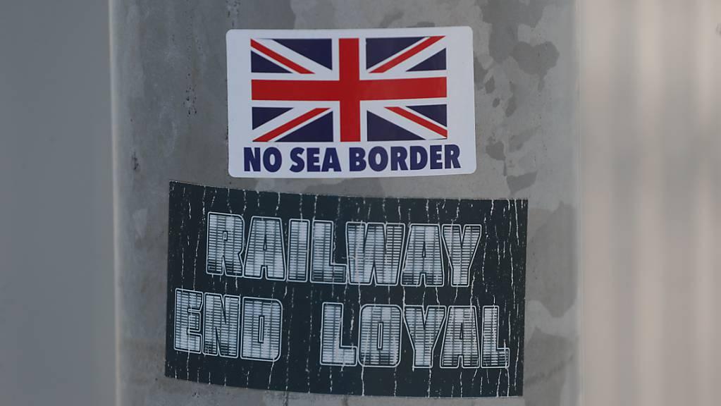 Ein Protestaufkleber mit der Aufschrift «No Sea Border» klebt auf einem Laternenpfahl. Im Streit um die Brexit-Sonderregeln für Nordirland hat die EU-Kommissionspräsidentin von der Leyen dem britischen Premierminister Boris Johnson eine deutliche Absage für mögliche Neuverhandlungen erteilt. Foto: Brian Lawless/PA Wire/dpa