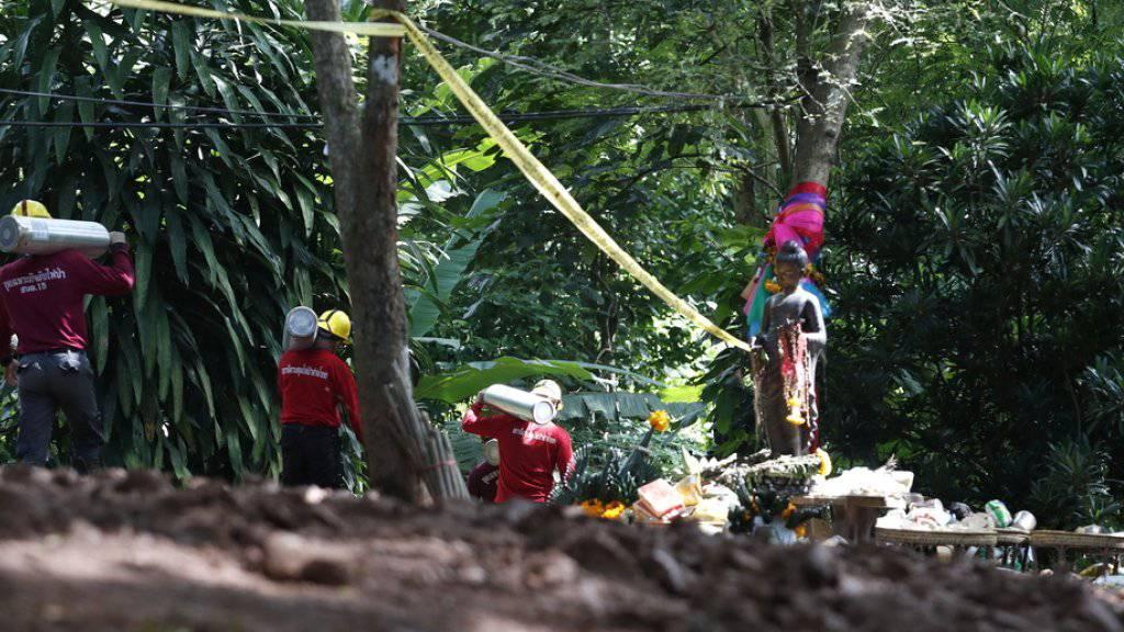 Rettungskräfte mit Sauerstoffflaschen am Donnerstag vor der Höhle - vor der sich reges Leben entfaltet hat.