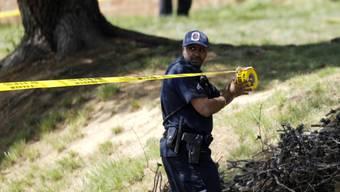 Ein Polizist sperrt einen Tatort ab (Symbolbild)