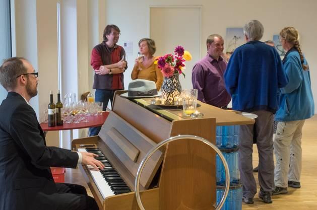 Pianist Felix Stocker und Vernissage Besucher.