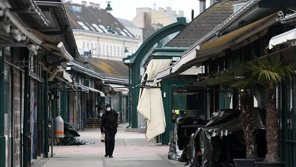 Ein Mann geht über den geschlossenen Wiener Naschmarkt. In der Landeshauptstadt und anderen östliche Regionen Österreichs soll der Betrieb rund um Ostern «massiv» heruntergefahren werden. Foto: Helmut Fohringer/APA/dpa