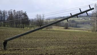 Ein Strommast liegt in einem Feld, umgeweht während des Sturms Sabine in Courtetelle, Kanton Jura.