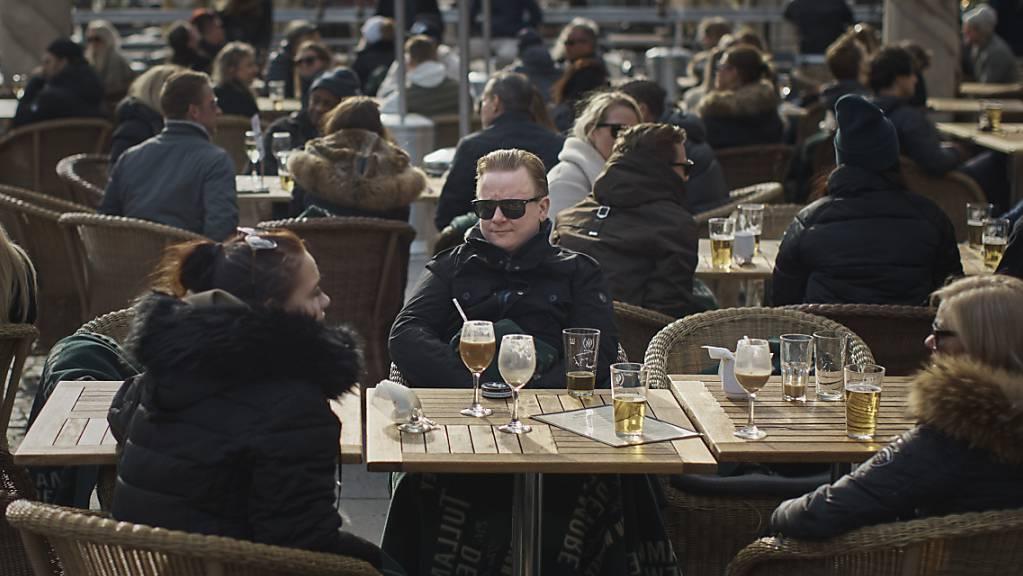 ARCHIV - Menschen sitzen vor einem Restaurant am Bürgerplatz in Stockholm. Foto: Andres Kudacki/AP/dpa