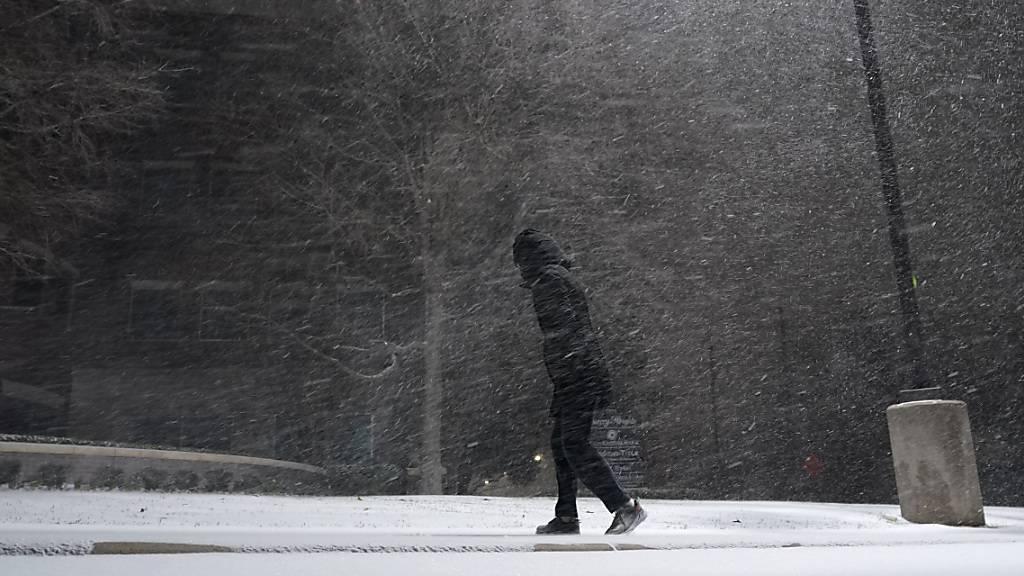 Eine Frau geht durch fallenden Schnee. Im südlichen US-Bundesstaat Texas sind wegen ungewöhnlich kalten Winterwetters Hunderttausende Menschen mindestens zeitweise ohne Strom gewesen. Foto: Eric Gay/AP/dpa