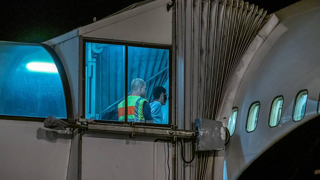 ARCHIV - Polizeibeamte begleiten einen Afghanen auf dem Flughafen Leipzig-Halle in ein Charterflugzeug. Deutschland schiebt vorerst keine Menschen mehr nach Afghanistan ab. Foto: Michael Kappeler/dpa