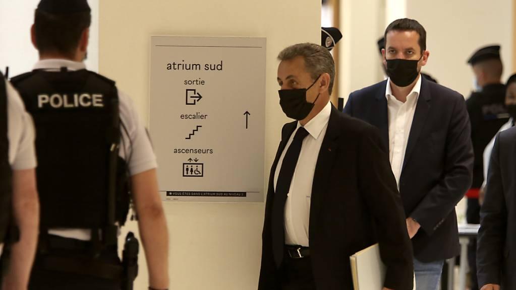 Frankreichs ehemaliger Präsident Nicolas Sarkozy (M) kommt in einem Pariser Gerichtsgebäude an. Es ist die Fortsetzung der Verhandlungen im Prozess gegen den früheren Präsidenten wegen mutmaßlich illegaler Wahlkampf-Finanzierung im Jahr 2012. Foto: Rafael Yaghobzadeh/AP/dpa
