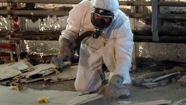 Ein Arbeiter im Schutzanzug zerkleinert Asbestteile (Archiv)
