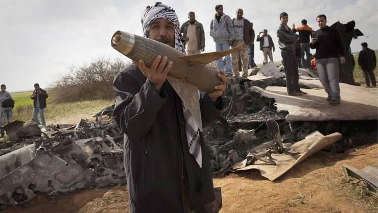 Libyer posieren mit Wrackteilen des abgestürzten Kampfjets.