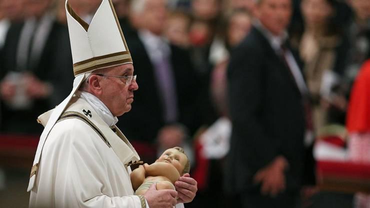 Papst Franziskus trägt die Figur des Jesuskindes.