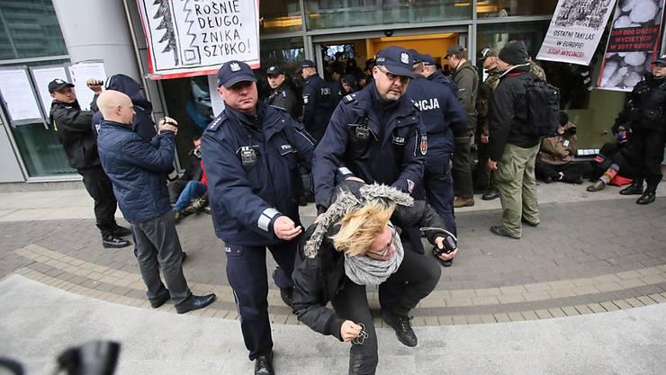 Polnische Polizisten gehen gewaltsam gegen Umweltaktivisten vor, die in Warschau gegen die Abholzung des Bialowieza-Urwalds protestieren.