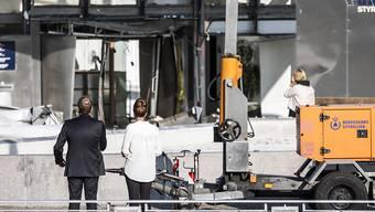 Steuerverwaltungsdirektorin Merete Agergaard und Steuerminister Morten Bodskov begutachten nach einer Explosion die Schäden an der Fassade des Steuerverwaltungsgebäudes in Kopenhagen.