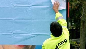 Ein Mitarbeiter der APG bringt ein Wahlplakat an (Archiv)