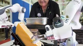 Ein Roboter streicht eine Portion Raclette auf einen Teller. Das Gerät wurde am Samstag an einer Messe in Martigny VS vorgestellt.