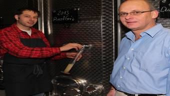 Heinz Simmen (links) und Hans-Peter Kuhn messen mit der Öchslewaage die Öchsle des Pinot gris.