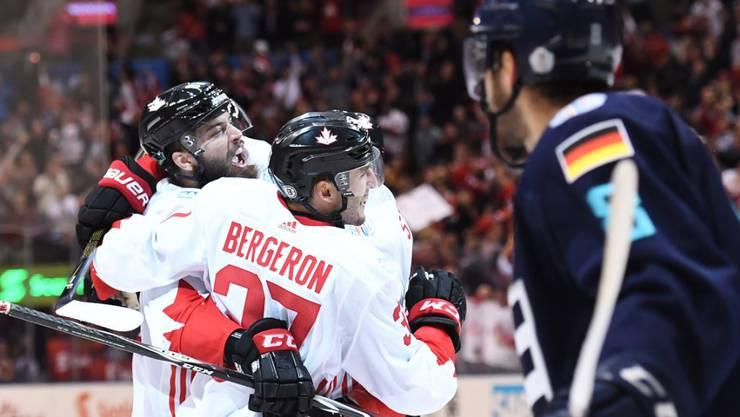 Kanadas Torschütze Patrice Bergeron feiert zusammen mit Teamkollegen den späten 1:1-Ausgleich, Europas Stürmer Tobias Rieder schaut zu